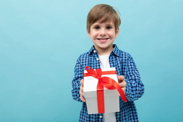 Cute boy in a plaid shirt holds out his lover's gift on a light blue background