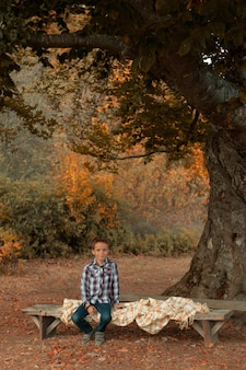 Cute boy in a plaid shirt sits on a bench under an old oak tree in autumn