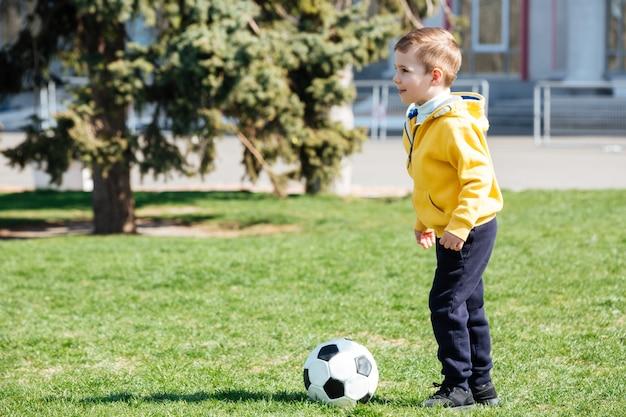 かわいい男の子が公園でサッカーをプレイ