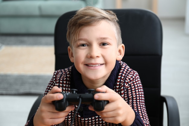 Cute boy playing video game at home