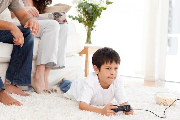 かわいい男の子、ビデオゲーム、床、家、床に横たわっている