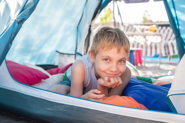Cute boy playing with pillow inside a tent at backyard