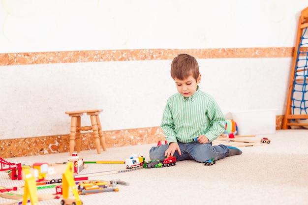 Милый мальчик играет с игрушечной железной дорогой на полу