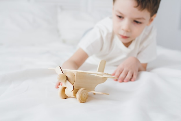 Cute boy playing with wooden airplane sitting on the bed