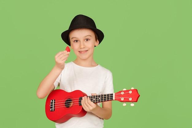 かわいい男の子がウクレレを弾きます。音楽を楽しんでいる幸せな子供。ウクレレを弾くことを学ぶ学生。緑の背景に分離された夏の帽子のファッショナブルな男の子。