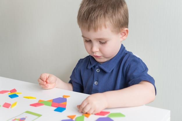 Милый мальчик играет в деревянную игру tangram. творческие и развивающие игры на карантине. копировать пространство