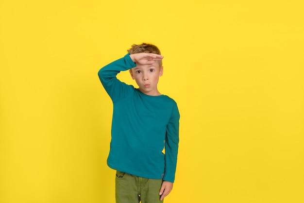 이마에 손바닥을 대고 먼 곳을 바라보는 노란 벽에 포즈를 취한 귀여운 소년