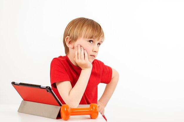 Милый мальчик подготовился к утренней онлайн-тренировке. детский спорт. онлайн-тренировки дома.