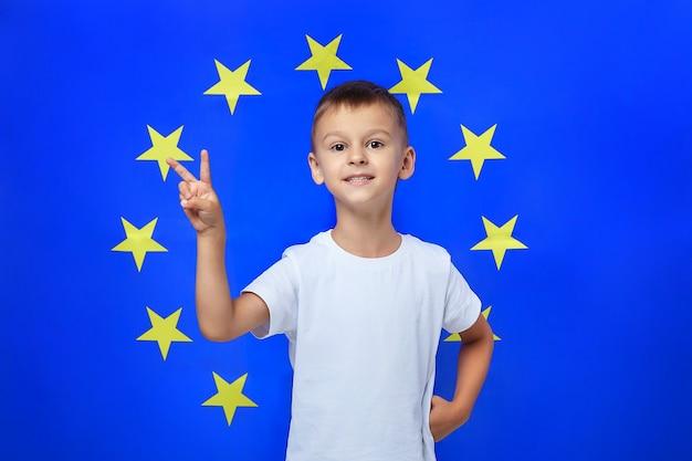 Симпатичный мальчик складывает пальцы в v-образную форму против европейского союза
