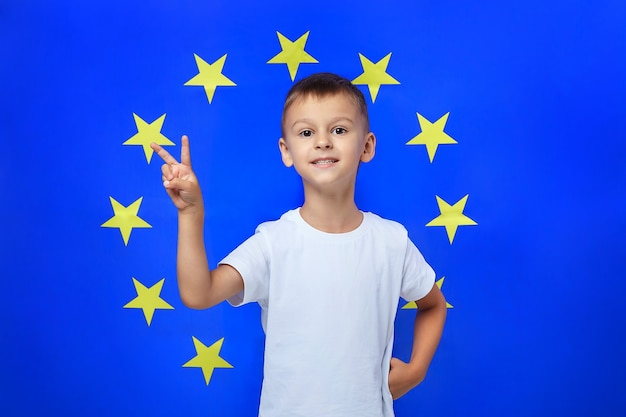 Cute boy puts his fingers together in a v shape against the of the european union