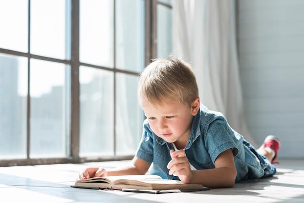 Cute boy reading book near the window