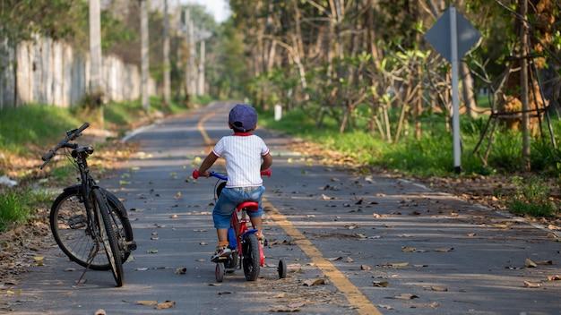 A cute boy riding a bicycle near his father's big bike.