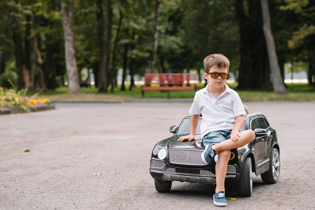 Cute boy in riding a black electric car in the park