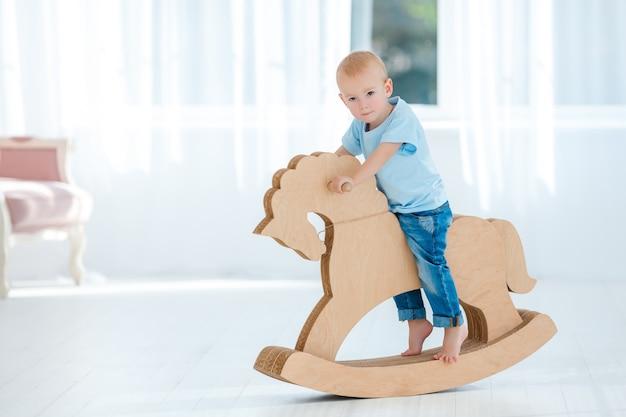 木製の手作りの馬に揺れるかわいい男の子