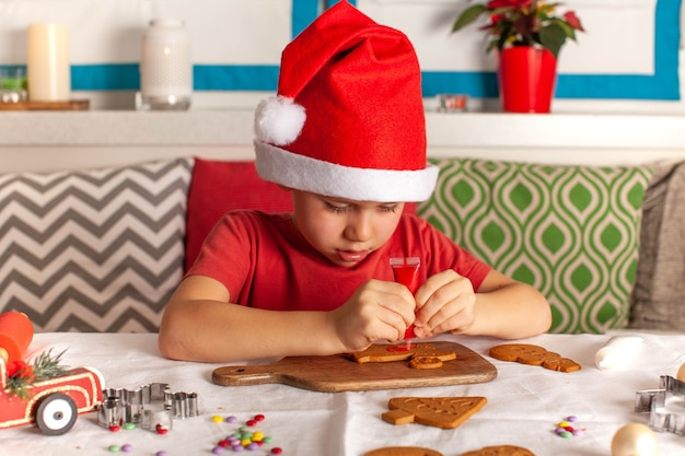 Cute boy in santa claus hat carefully decorates gingerbread
