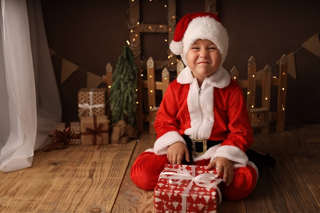 Cute boy in santa costume holds a new year gift