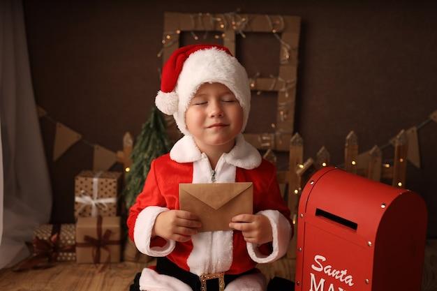 Cute boy in santa costume sends a letter to santa claus