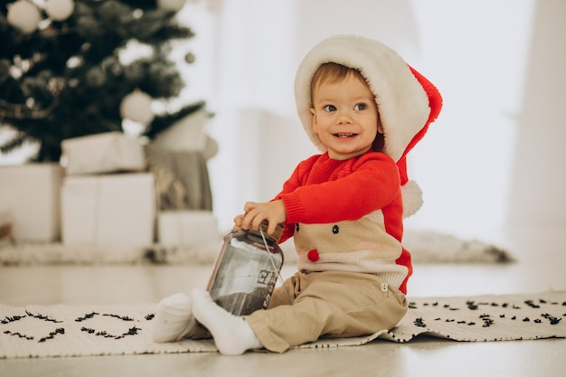 Cute boy in santa hat openning presents on christmas