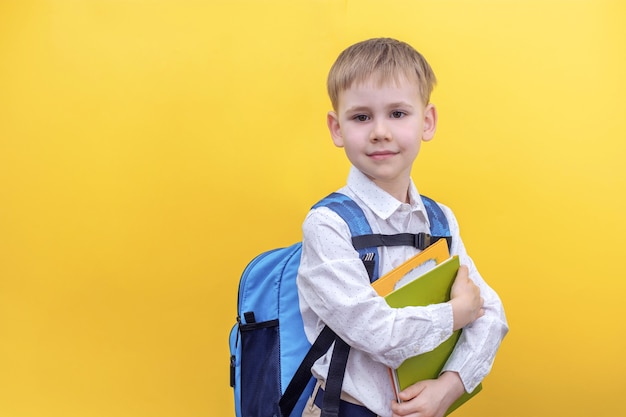 A cute boy in a shirt with a backpack on his back holding textbooks on yellow