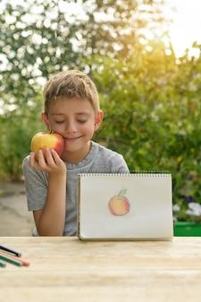 귀여운 소년이 그려진 사과를 보여줍니다. 야외. 백그라운드에서 정원. 창조적 인 개념.