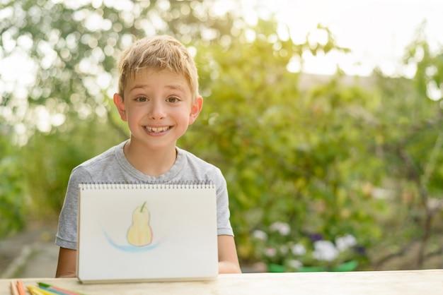Cute boy shows drawn pear.