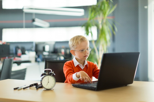 Cute boy sit at the desk in the office and uses computer