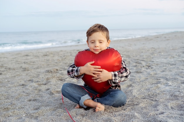 Cute boy sits on the beach and hugs a red heart balloon.