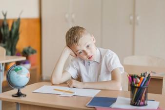 Cute boy sitting at desk in classroom