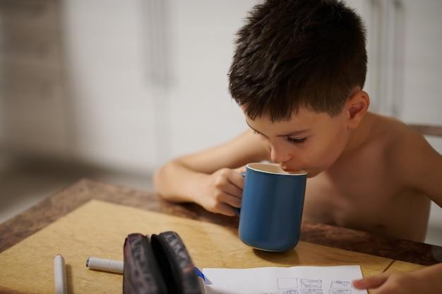 테이블에 앉아서 뜨거운 음료를 마시는 귀여운 소년