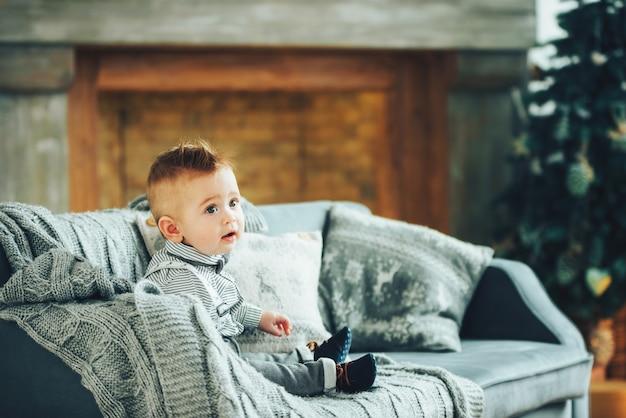 Милый мальчик сидит на диване, накрытом одеялом на фоне рождественского украшения