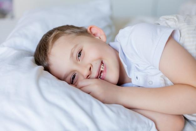 침대에서 자 고 귀여운 소년입니다. 아침.