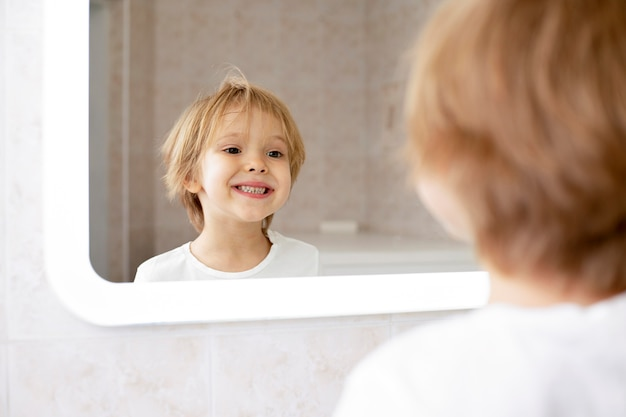 Милый мальчик, улыбаясь в зеркало