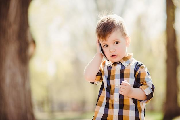 귀여운 소년 공원에서 휴대 전화로 말하십시오