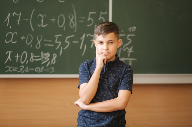 칠판의 교실 배경에서 귀여운 소년 스탠드. 교육. 초등학교. 생각하는 소년