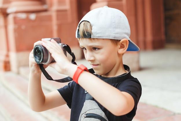 Милый мальчик фотографирует в городе. школьный проект для детей на летние каникулы. будущая профессия.