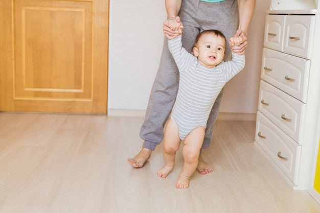 Cute boy taking first steps holding mother's hands.
