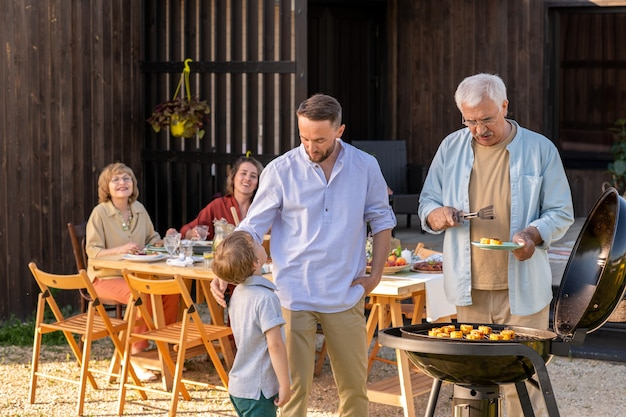 Cute boy talking to his father by grill during family gathering