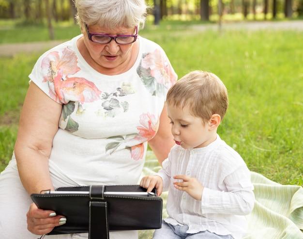 Милый мальчик учит бабушку в очках пользоваться современными умными устройствами на открытом воздухе