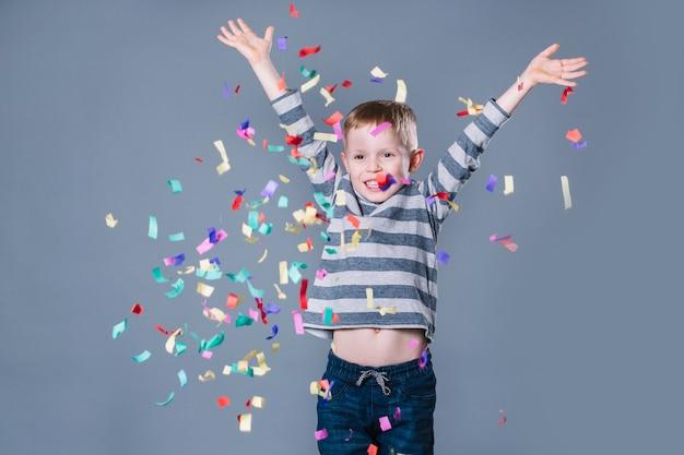 Cute boy throwing confetti Premium Photo