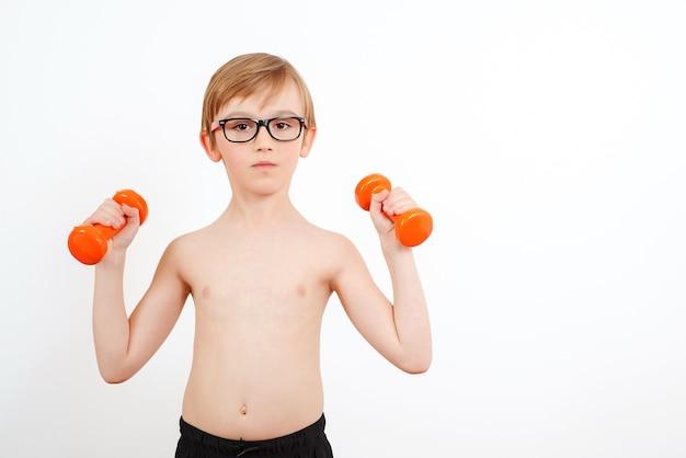 白で隔離、ダンベルでトレーニングかわいい男の子。子供のフィットネス。私たちの体を健康に保つ。