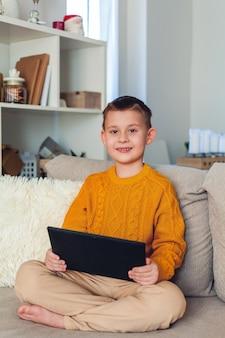 귀여운 소년은 태블릿을 사용합니다. 소년은 비디오 링크로 말합니다. 건강 격리. 집.