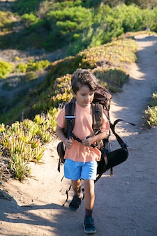 Cute boy walking on countryside path and carrying huge backpack. front view, full length. childhood or adventure travel concept