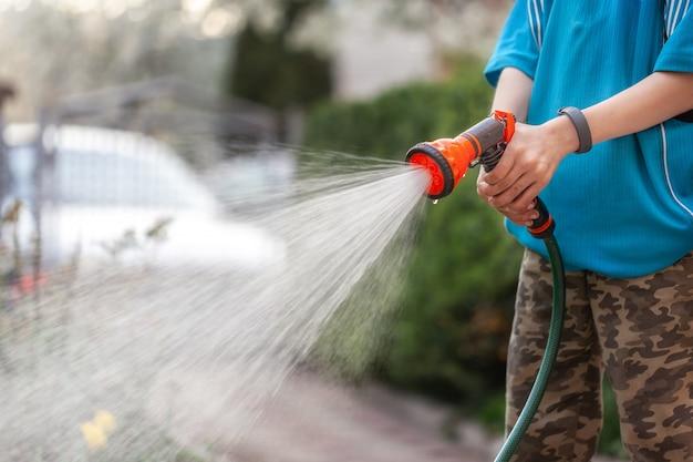 Милый мальчик поливает растения из шланга, делает дождь в саду. ребенок помогает родителям выращивать цветы.