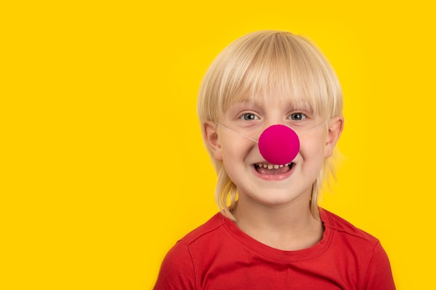 Cute boy wearing clown nose and smiling