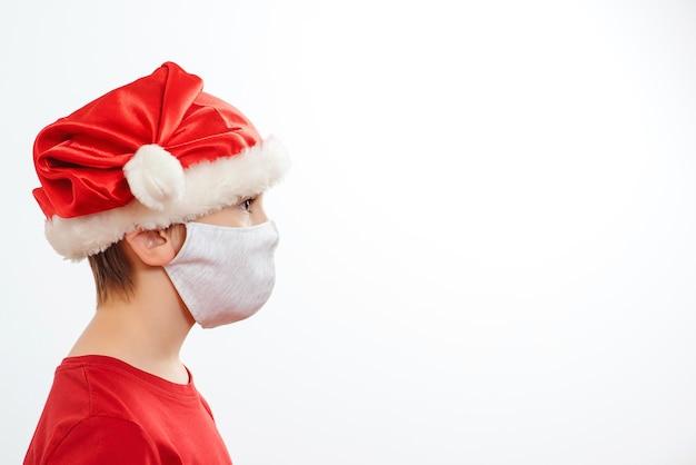 コロナウイルスから保護するためにフェイスマスクを身に着けているかわいい男の子。コロナウイルス検疫中の冬休み。コピースペースで、白い背景で隔離のクリスマス帽子をかぶっている子供。