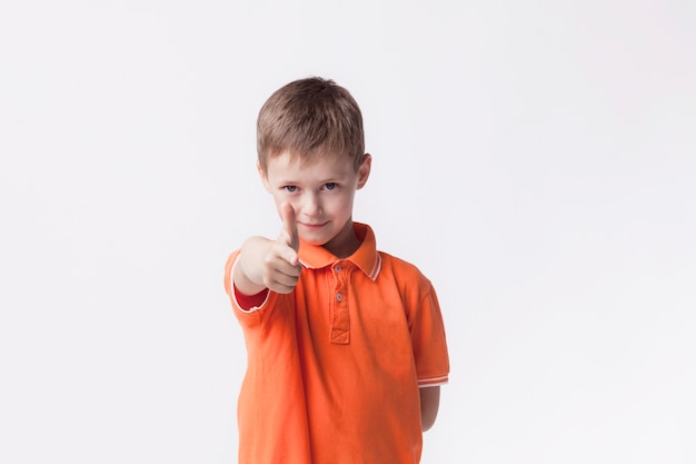 Cute boy wearing orange t-shirt pointing at camera on white wall