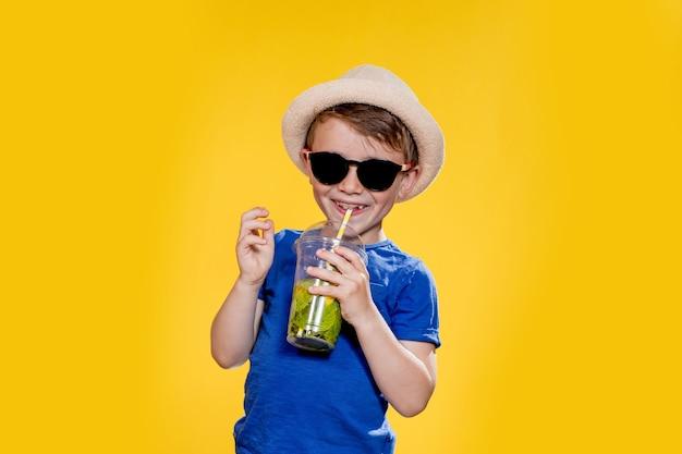 Милый мальчик в солнцезащитных очках и наслаждаясь, попивая лимонад