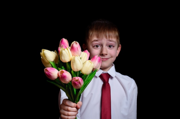 Cute boy in white shirt gives a bouquet of tulips. isolate