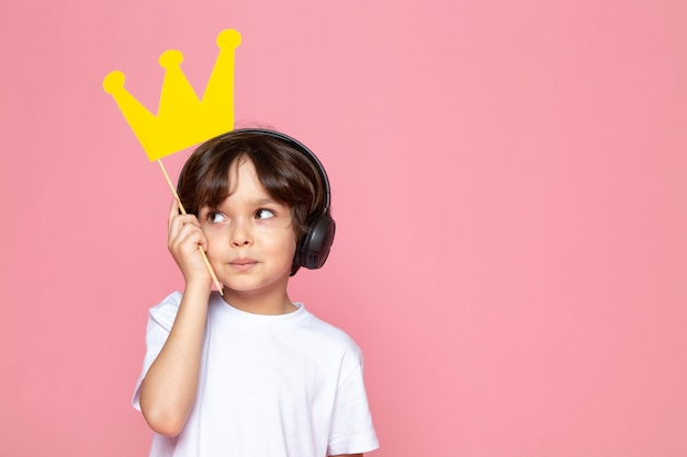 Cute boy in white t-shirt holding yellow crown