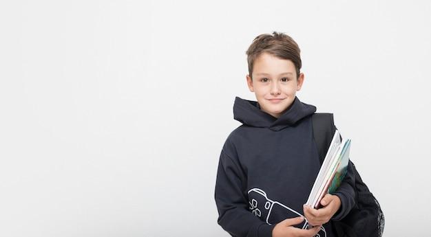 Милый мальчик с рюкзаком и книгой и блокнотом в руках на белом